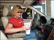Angela Muggenburg gets her lunch at a drive-through McDonald's in Springfield, Mo. The busy mom is one among many Americans whose chaotic schedules have them picking up more than an occasional meal to eat on the go.