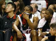 Miami Heat players, from left, Wang Zhi-Zhi, Udonis Haslem and Rafer Alston watch as their team falls behind Indiana during Game 6 of their Eastern Conference semifinal series. The Pacers won the game, 73-70, Tuesday night in Miami to win the best-of-seven series, 4-2.