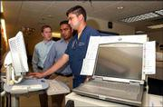 Cerner Corp. representatives Todd Willemsen, left, and Amit Raghavan, center, show Dr. Chris Vega how to use a new computer system at Lawrence Memorial Hospital. Vega was learning on Wednesday how to use the system that contains patients' medical records.