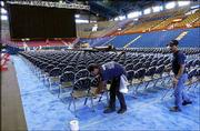 Ramon Rivera, left, and Ramiro Gonzalez put the finishing touches on the seating arrangements at Allen Fieldhouse for Friday's lecture by former President Bill Clinton. The stage, seating, lighting and sound were set up Wednesday in the fieldhouse for the inaugural Dole Lecture.
