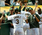 Teammates greet Oakland's Eric Chavez (3) after his two-run homer in the ninth inning tied the game against Kansas City. The A's won, 5-4 in 11 innings, Saturday in Oakland, Calif.