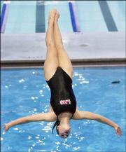 Lawrence High senior Ellie Lloyd performs a reverse dive. Lloyd placed 13th in diving competition Saturday in Manhattan.
