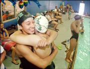 Free State High sophomore Ashley Robinson, left, hugs Wichita Trinity's Caroline Bruce after Robinson won the 500-yard freestyle at the Kansas state swimming and diving championships. Robinson also won the 100 butterfly Saturday in Manhattan.