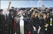 Champagne flies through the air as students from Kansas University's School of Medicine celebrate at the conclusion of KU's commencement ceremony.