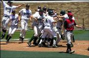 The Free State High baseball team celebrates its extra-inning victory over Blue Valley West. The Firebirds' 3-2, eight-inning win Friday at Hoglund Ballpark advanced FSHS to the Class 6A state semifinals. BV West pitcher Lance Hoge is at right.
