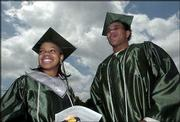 Free State High School seniors Kamesha Moore, left, and Tyree Payne participate in the Class of 2004 commencement ceremony. They received their diplomas May 15 during the ceremony at Kansas University's Memorial Stadium.