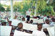 "Director Robert Foster leads the Lawrence City Band in the ""Star Spangled Banner"" while a park full of people listens. The band kicks off its 2004 summer season at 8 p.m. Wednesday in South Park, 11th and Massachusetts."