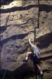 JOSH WICOFF, a Kansas University sophomore from Lenexa, climbs the rock wall in the Student Recreation Fitness Center. The center opened in September 2003.