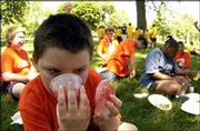 Forest Lassman, 9, chugs a cup of applesauce during a picnic in South Park. Lassman, a member of the Boys & Girls Club of Lawrence, attended the picnic Wednesday. Organizers hoped the event would raise awareness of the effect that cutting after-school programs would have on local youth.