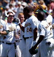 Oakland's Mark Kotsay, left, is congratulated by teammates Jermaine Dye, center, and Marc McLemore, right, after Kotsay hit a game-winning home run against the White Sox. The Athletics won, 3-2 in 10 innings, Wednesday in Oakland, Calif.