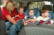 Jana Fevurly, of Scottsdale, Ariz., left, buckles in her three sons Jack, 5 1/2, Jake, 1 1/2, and Justin, 4, before heading out on the road in downtown Lawrence. A new survey gives Kansas low marks for its efforts to keep children safe with stringent seat belt laws. Jana and her husband, John, Kansas University alumni, were in Lawrence for a visit.