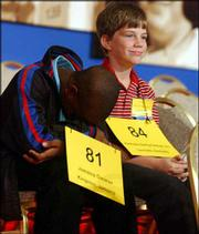 Cornel Andre Grey, 11, of Portmore St. Catherine, Jamaica, left, and John Tamplin, 11, of Louisville, Ky., wait to participate in the 77th annual National Spelling Bee in Washington, D.C.