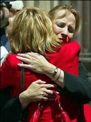 Peggie Pietrowicz, left, hugs her sister, Lynne Gist, during a lunch break in the penalty phase of the state murder trial of convicted Oklahoma City bombing conspirator Terry Nichols, in McAlester, Okla. Pietrowicz and Gist, shown Wednesday, lost their younger sister, Karen Gist Carr, in the 1995 Oklahoma City bombing.