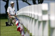 U.S. D-Day veteran Robert Kenney, from Tallassee, Ala., pays his respects at the American war cemetery at Colleville-sur-Mer in Normandy, France. The 83-year-old veteran of the 35th Infantry Division was in Normandy on Saturday for the 60th anniversary commemoration of D-Day.