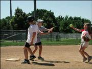 Third-grader Anna Meissbach gets ready to throw to sixth-grader Krista Diedel at the Lawrence High softball camp.
