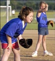 Rockets players Ella Shupart, 7, left, and Haley Ryan, 8, play infield during their game against the Mighty Mighty Girls on Thursday at Youth Sports Inc. fields. Both teams are part of the Lawrence Parks and Recreation leagues.