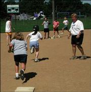 Sixth-grader Emily Newman tries to get out of a rundown while camp director Reenie Stogsdill looks on.