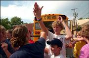 "Kirby Beneventi, 19, left, high-fives Chase Hoag, 13, after Hoag and other members of the First Christian Church Youth Group arrive in Lawrence after having been stuck since last Friday in Colorado. Beneventi was also with the group but got a ride home on Saturday. The school bus with the rest of the youth group returned Thursday afternoon. In foreground at bottom is youth group member Zach ""Chewey"" Canote, 12."