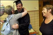 Graduate Lonnie Biggers gets a hug from Linda Kucza, an instructor at the Adult Learning Center, after receiving his General Educational Development diploma. Biggers was one of 78 students to pass the GED test this academic year, 28 of whom participated in the graduation ceremony Wednesday at Lawrence High School. Biggers' wife, Pam, is at right.