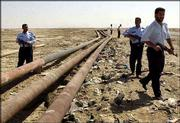 Armed Iraqi police patrol along oil pipelines outside of the town of Faw, Iraq. Saboteurs blasted a key pipeline Wednesday for the second time in as many days, halting Iraq's oil exports, officials said.
