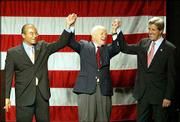 Democratic presidential candidate Sen. John Kerry, D-Mass., right, raises his hands with Columbus, Ohio, Mayor Michael Coleman, left, and former Sen. John Glenn, D-Ohio, before a reception in Columbus. Wednesday, during his Columbus visit, Kerry announced he had raised more than $100 million for his candidacy in the last three months.