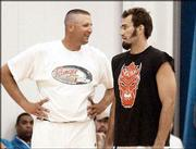Former Kansas University basketball players Greg Ostertag, left, and Scot Pollard chat before a pickup game against current Jayhawks. The former KU players helped out at coach Bill Self's camp Wednesday at Horejsi Center.