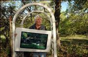 Robert Sudlow displays a painting he created at a pond near his hillside home south of Lawrence. About 29 Sudlow works in the private collection of Topekan Horace Eubank will be on view Monday through July 30 in the Sabatini Gallery at the Topeka and Shawnee County Public Library.