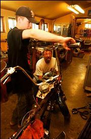 "Casey Pollard, 16, of Lecompton, a mechanic at Hog Works, gets help from owner Randy Lester. The reality-television show ""American Chopper"" has provided a boost in business for the motorcycle industry."