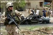 A U.S. soldier stands guard in front of a burned-out car at the scene of an explosion in Baghdad, Iraq. A car bomb exploded May 31 near the headquarters of the U.S.-run occupation authority, killing at least two people. Many firms working on contracts in Iraq are seeing the price of insurance for employees there jump markedly, after the deaths of several contract workers in recent months.