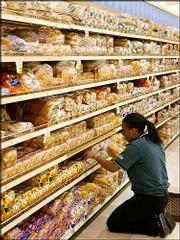 Shancell Ward, of Washington, D.C., stacks white bread on shelves at a grocery store in Washington. Scientists say white bread and other refined grains seem to go to the gut and hang out as belly fat.