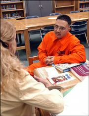 Tomas Villareal, right, a prisoner at the Penitentiary of New Mexico, talks with Melody Whitehead, left, transition coordinator for the Education Department at the penitentiary. Whitehead runs two programs that help Villareal stay in touch with his children and learn to be a better father.
