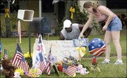 Carlton and Stacey Hadley, of Merritt Island, Fla., leave a sign showing their support of Paul Johnson Jr. at a makeshift memorial in front of the home of Johnson's son, Paul Johnson III, in Port St. John, Fla.