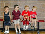 From left, Logan Farmer, 4, Stephen Cory, 4, Zebulun Huseman, 4, and Gad Huseman, 4, wait for their turn to hit during Thursday's blastball session at the East Lawrence Recreation Center.