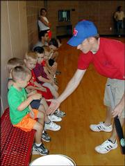 Coach Ryan Martin offers Alexander Weber, 4, a high-five Thursday during blastball class at the East Lawrence Recreation Center while other players look on.