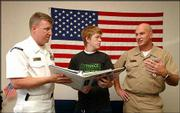 U.S. Navy recruiters Rob Parsons, left, and Dave Iltzsch, right, talk with Andy Lowder 17, a 2004 Lawrence High School graduate, about the options in the Navy. Lowder was checking out education prospects and job possibilities that come with military service.