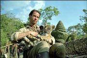 """Antiquities hunter Aidan McRory, played by Guy Pearce, removes one of a set of twin tiger cubs from a looted temple in this scene from the adventure drama """"Two Brothers."""""""