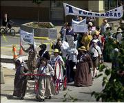 Participants in the Temperance Rally make their way through downtown Lawrence, exhorting residents to give up booze.