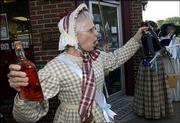 "Christine Reinhard, of Lawrence, finds ""illicit spirits"" at the Round Corner Drug Store during the Temperance Rally from the Watkins Community Museum of History to the Free State Brewing Co. Men and women dressed in period clothing marched Friday down Massachusetts Street, pouring out the spirits they found at local ""groggeries"" along the way."