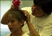 Sarah Chavez, 10, gets a helping hand with a hair accessory from her mother, before going on stage at the 23rd annual St. John's Mexican Fiesta. Friday night's events included dancing, music and authentic Mexican food. The Fiesta continues at 5:30 tonight on the grounds at St. John the Evangelist Catholic Church, 1234 Ky.