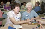 Gloria Bagby, left, and Darlene Lovelett look at some pictures before a salad luncheon given by the Lawrence Central United Methodist Women. The group invited other United Methodist Women groups on June 16 to share stories about the women's mission work at their churches.