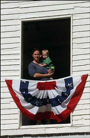 Carey Monaghan and her son Gavin, 20 months, get a bird's-eye view of Territorial Days festivities from Constitution Hall in Lecompton. The annual festival drew about 5,000 people to the northwest Douglas County town.
