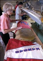"Shirley Menk, Wichita, steams a cape for a Kansas University band uniform at Fruhauf Uniforms. ""I love them (uniforms) all,"" said Menk, an employee at the uniform shop for 33 years, ""but this one is special.""<br> <a onclick= ""window.open(&squot;http://etc.lawrence.com/galleries/featherflock/3308_lores.html&squot;,&squot;Photo&squot;,&squot;height=650,width=750,screenX=10,screenY=10,&squot; + &squot;scrollbars,resizable&squot;); return false;"" target=""_new"" href= ""http://etc.lawrence.com/galleries/featherflock/3308_lores.html""><img alt=""*"" border=""0"" src=""http://www.kusports.com/art/icons/icon_photo.gif""> Photo gallery: New uniforms arrive</a><br>"