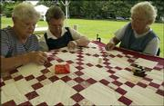 Clinton Lake Quilters, from left, Barbara Coggburn, of Baldwin, Martha Parker, of Clinton, and Lotta Bevitt, of Berryton, stitching on a quilt at the Chautauqua in South Park. The quilters showed their skills as part of a demonstration of the art of quilting during Tuesday's festivities. Tuesday was the final day of the Bleeding Kansas Chautauqua.