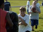 Lynn Robinson, 10, center, puts her shoulder into a pad to provide a block for Joseph Odrowski, 10, during a handoff and running drill at the Lawrence and Free State high school youth football camp. The camp was Tuesday at FSHS.