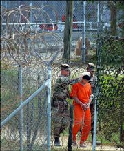A detainee is escorted to interrogation by U.S. military guards at Camp X-Ray at Guantanamo Bay U.S. Naval Base, Cuba, in this Feb. 27, 2002 file photo. Four detainees will face a military tribunal; they are the only suspects at the base to be formally charged.