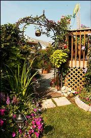 A metal archway leads to the back yard, bursting with flowers and a pond that has a small waterfall.