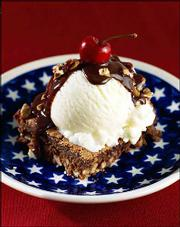 An All-American Chocolate Brownie Sundae combines ice cream and brownies, which may be near the top of any national popularity poll, separately or together. This version is made with bittersweet chocolate sauce, vanilla ice cream, pecans and fresh cherries.