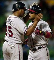 Atlanta's Charles Thomas, right, is congratulated by Andruw Jones after Thomas hit a two-run homer off Montreal starter Livan Hernandez. The Braves scored six times against Hernandez en route their 14-2 pasting of the Expos on Wednesday at Hiram Bithorn Stadium in San Juan, Puerto Rico.