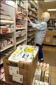 LaVerne Sinnett, an employee at Wood Oil Co. Store 5, stocks shelves. She said on Wednesday that the city's smoking ban in bars and restaurants, had not affected tobacco sales at the store, 920 N. Second St.