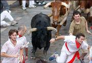Runners keep ahead of a fighting bull and a steer during the first San Fermin bull run in Pamplona, Spain. The San Fermin fiesta opened Wednesday.